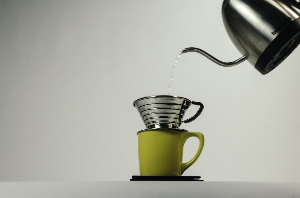 kettle pouring water on gray stainless steel cup on top on yellow ceramic mug