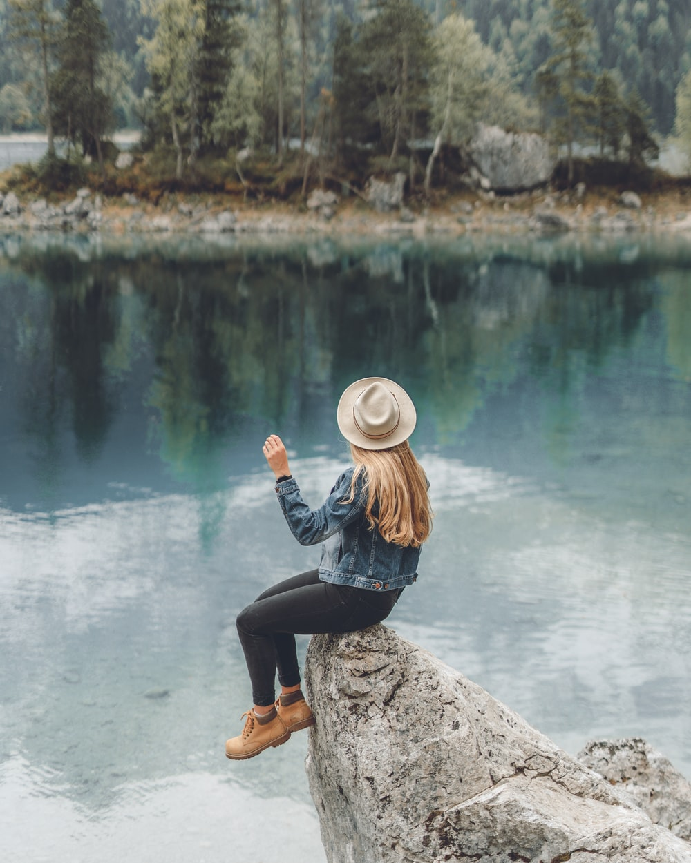 woman sitting on rock formation while facing on body of water during daytime