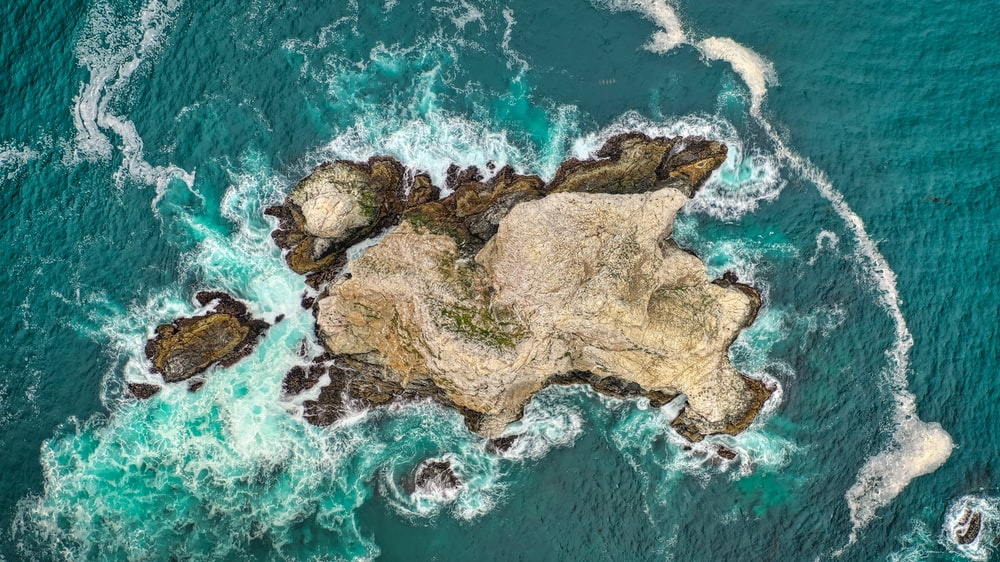bird's-eye photography of island surrounded by body of waqter