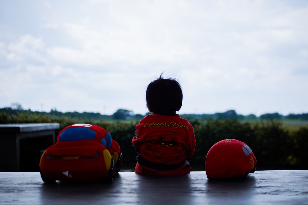 toddler sitting beside red car plush toy outdoors