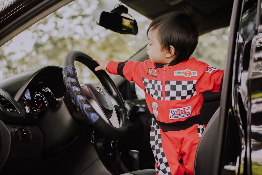 male toddler standing on driver's seat of a car