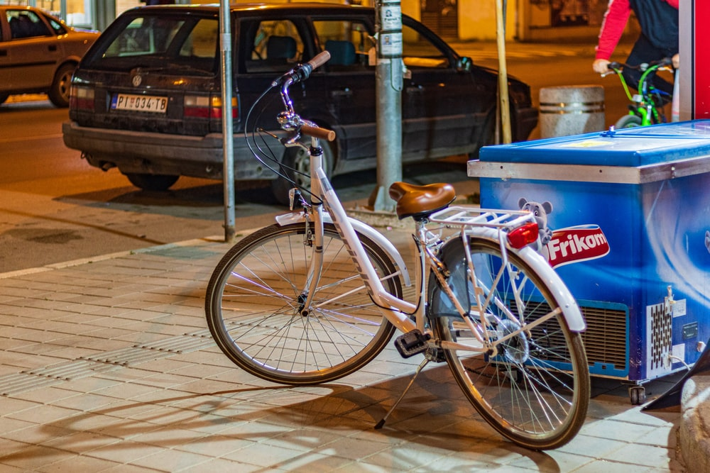 white and brown bike parked beside deep freezer
