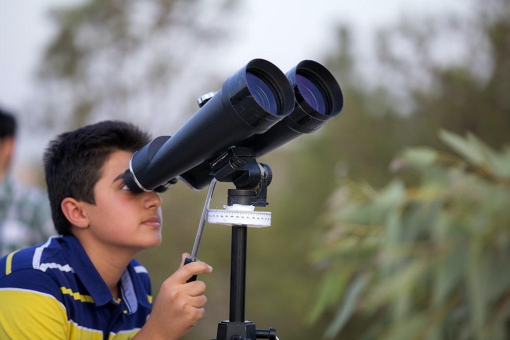 man using black binoculars