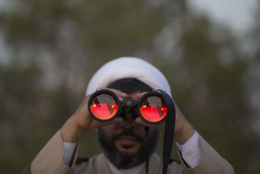 man holding black binoculars