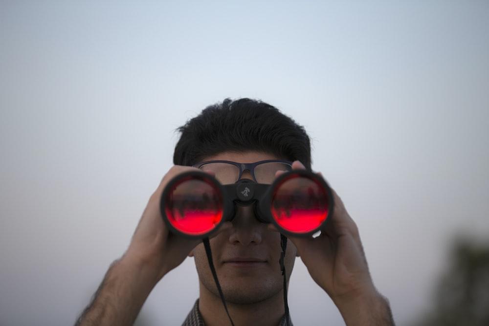 person holding black binoculars
