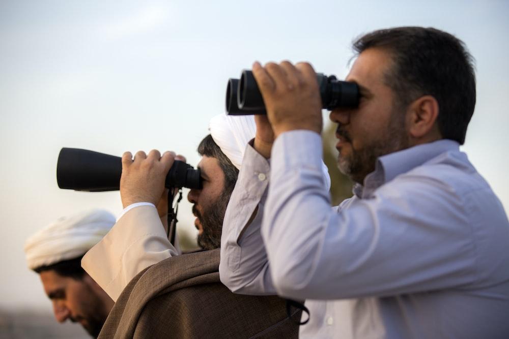 two men using binoculars