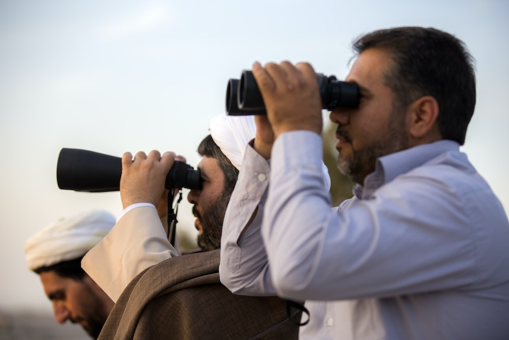 two men using binoculars