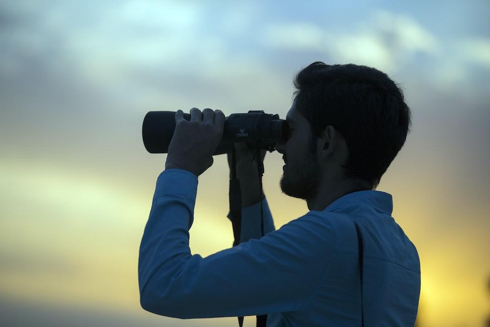 man holding telescope