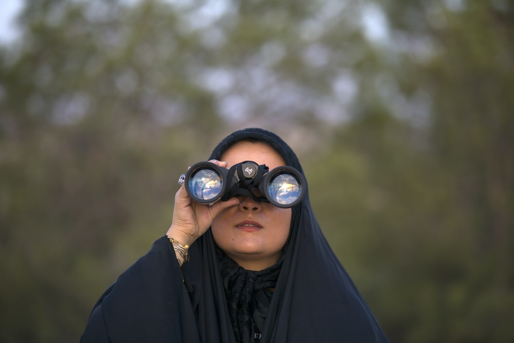 selective focus photo of woman using binoculars