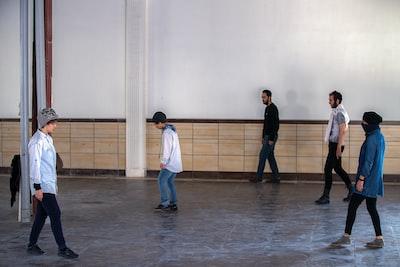 five men dancing at the studio performance art teams background