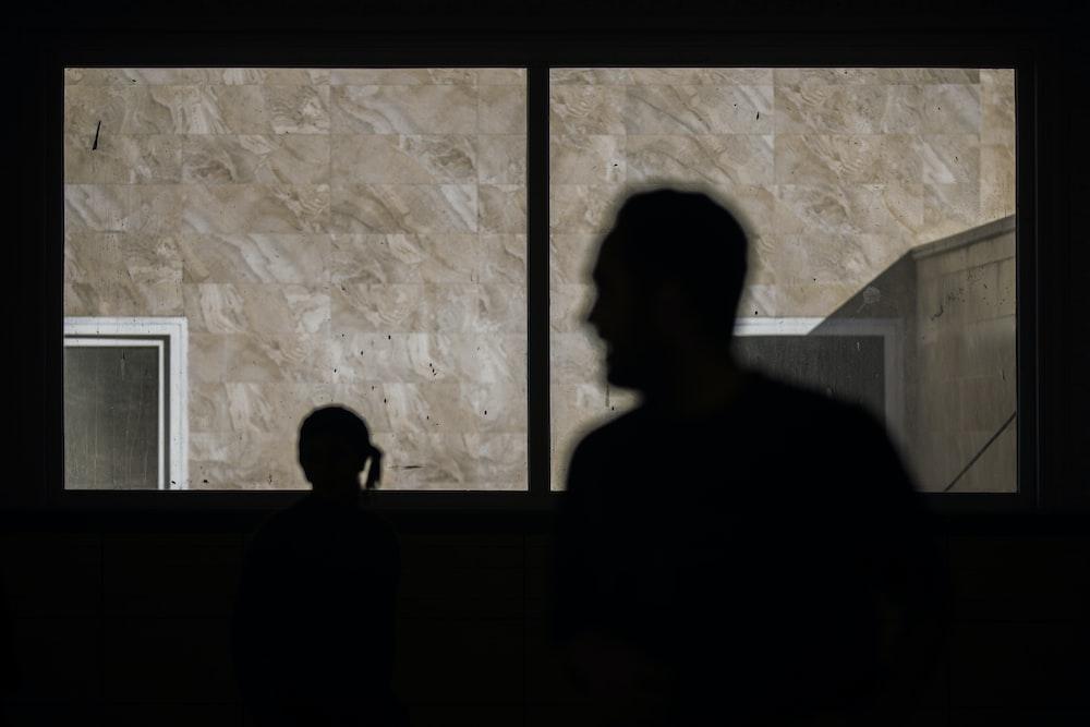 silhouette of man standing beside window