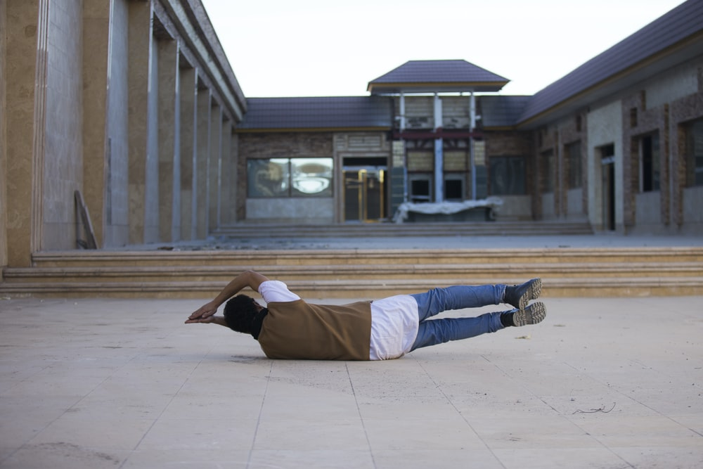 man lying in front of white and brown building