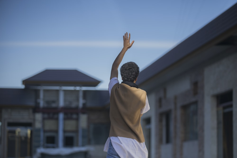 man standing and raising left hand during daytime