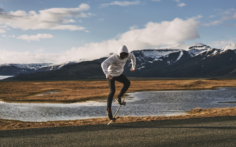 man doing tricks on skateboard near body of water