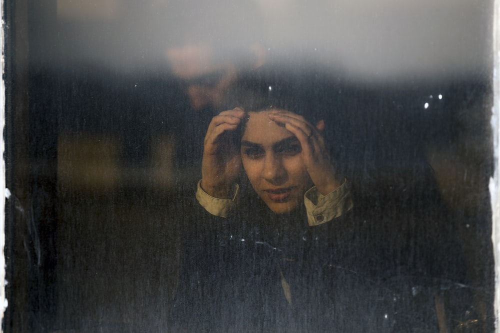 woman peaking on glass window panel