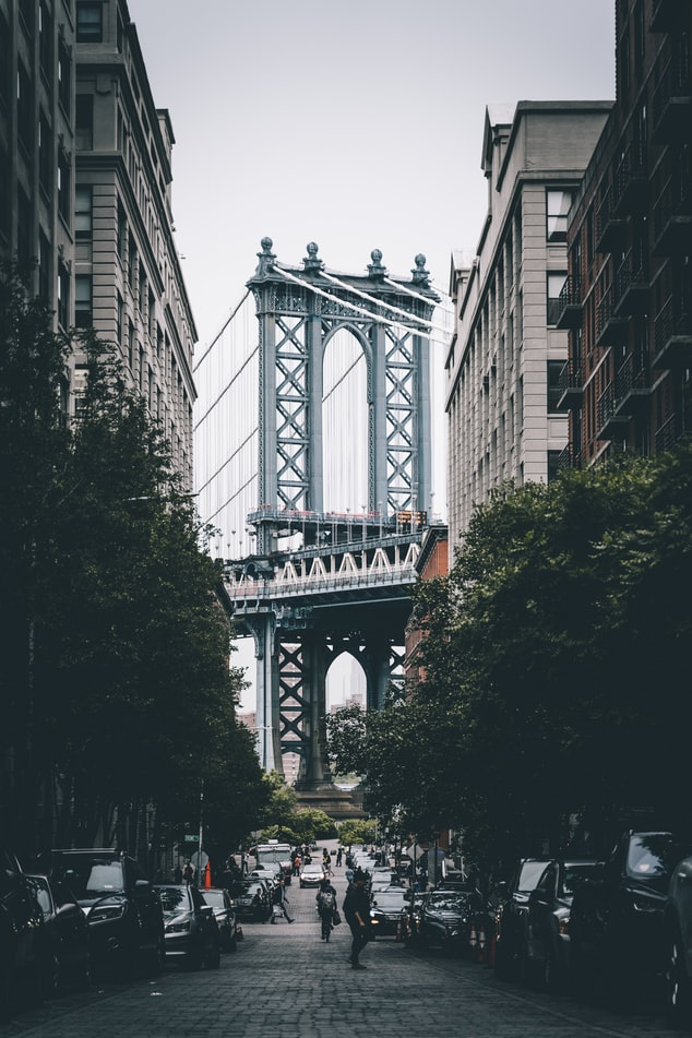a view of the Brooklyn Bridge between some buildings