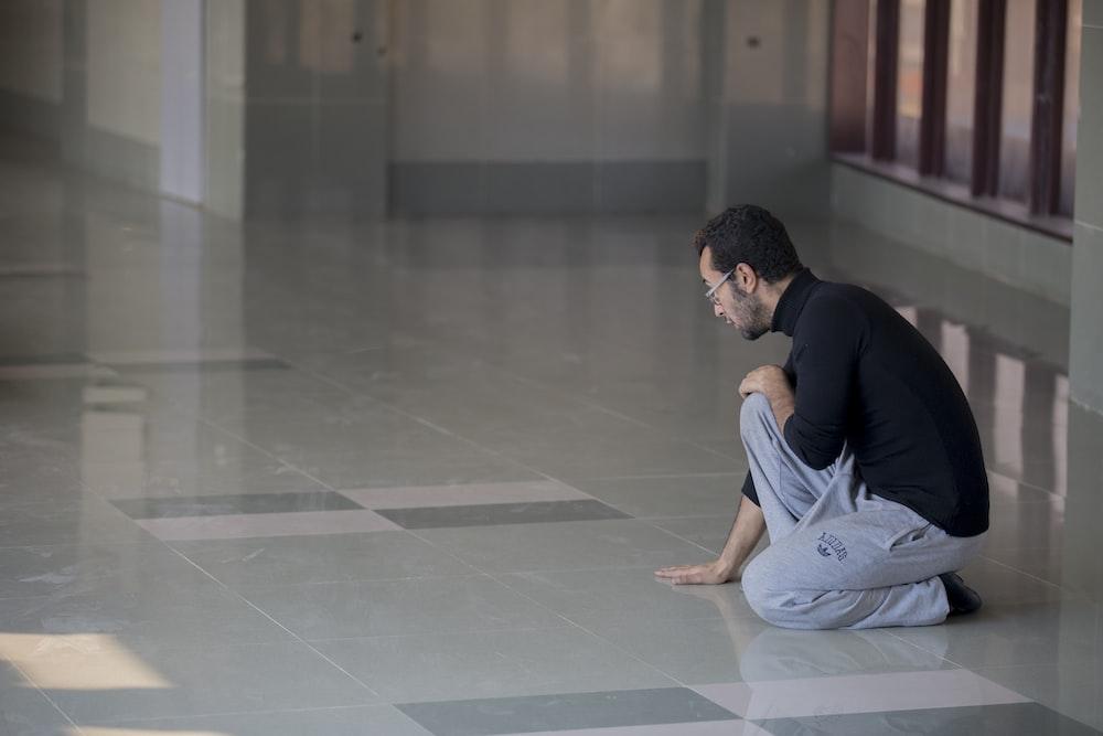 man squatting on floor