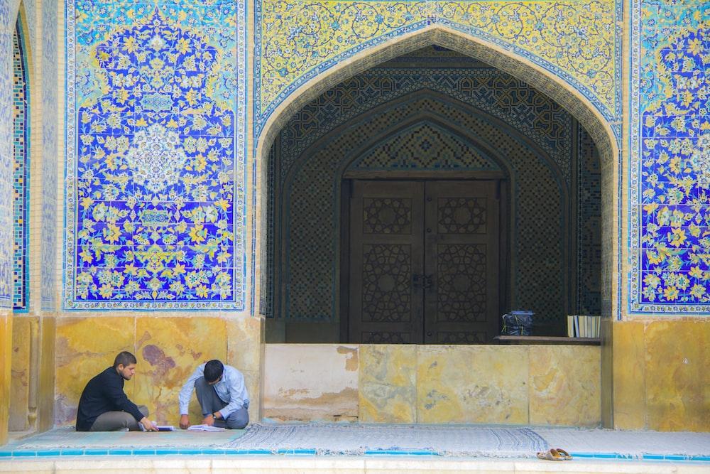 men sitting beside building