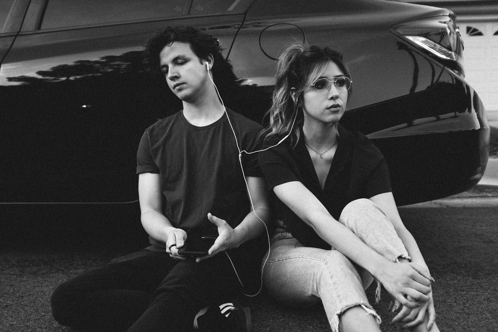 grayscale photo of man and woman leaning on vehicle