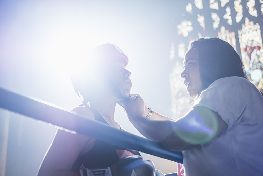 person fixing person's boxing headgear in the ring