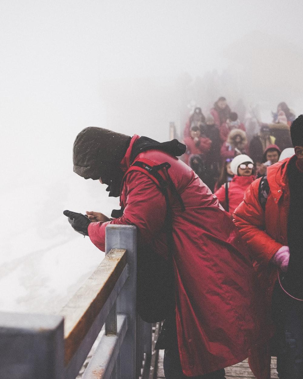 people wearing red jacket walking on bridge