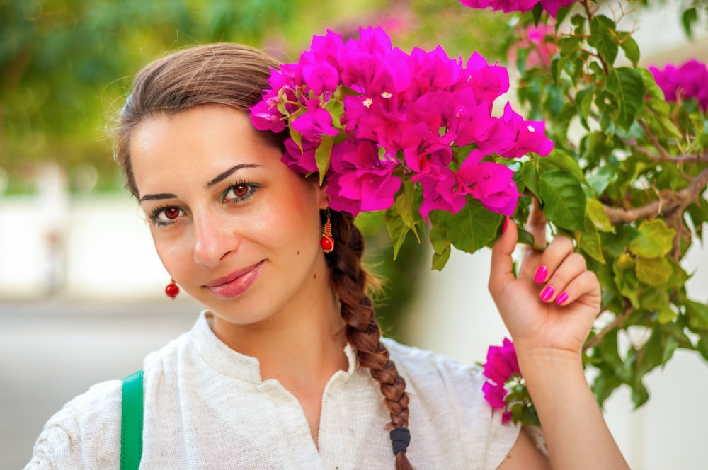 woman wearing white top holding pink flower