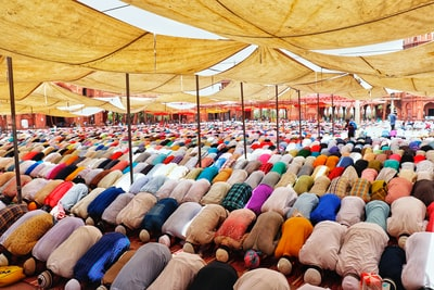 people bowing down inside canopy during day eid zoom background