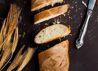 sliced of baked bread beside stainless steel bread knife