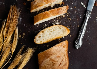sliced of baked bread beside stainless steel bread knife