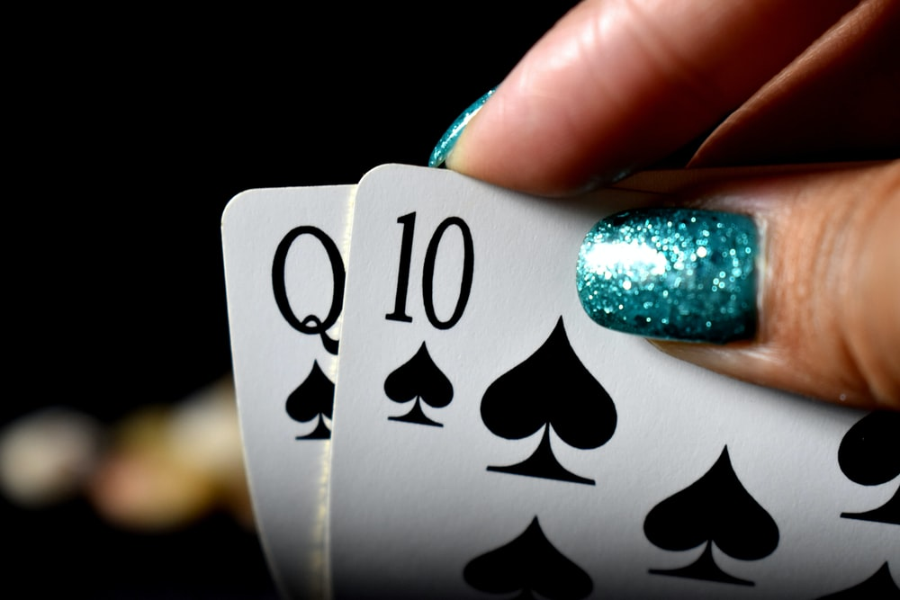 close-up photo of person holding two spade playing cards