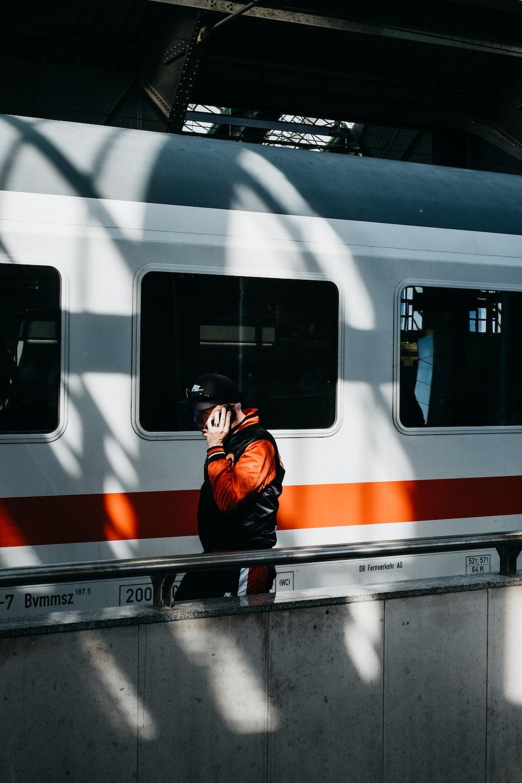 person walking near white and orange train