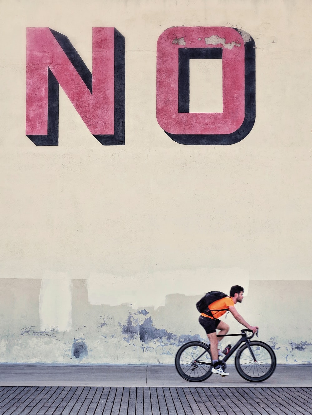 man riding bicycle beside wall with no text