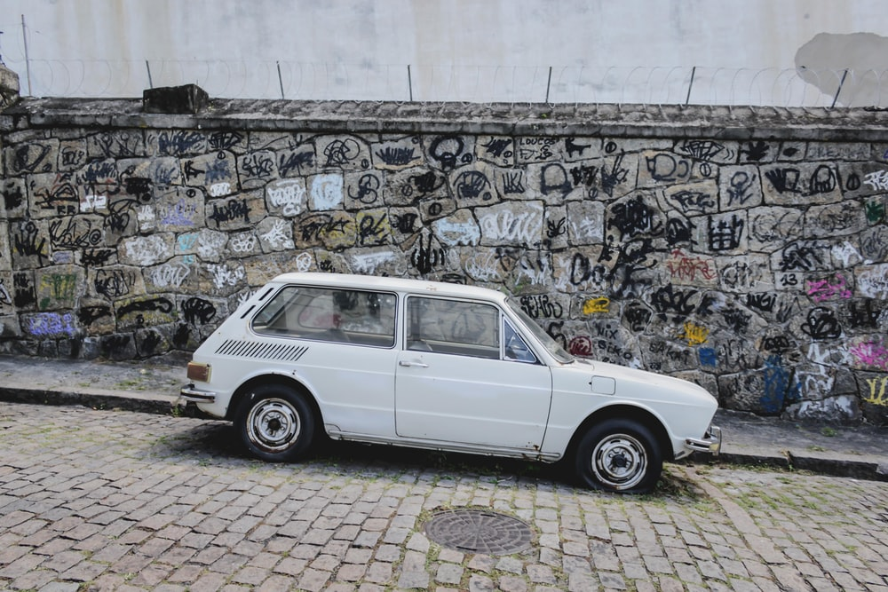 white car parked beside the road near wall with mural