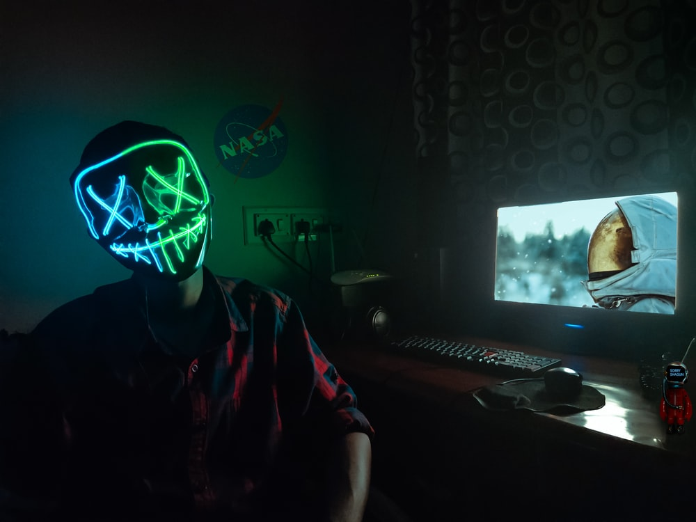 person in blue and green LEd mask sitting in front of turned-on computer monitor