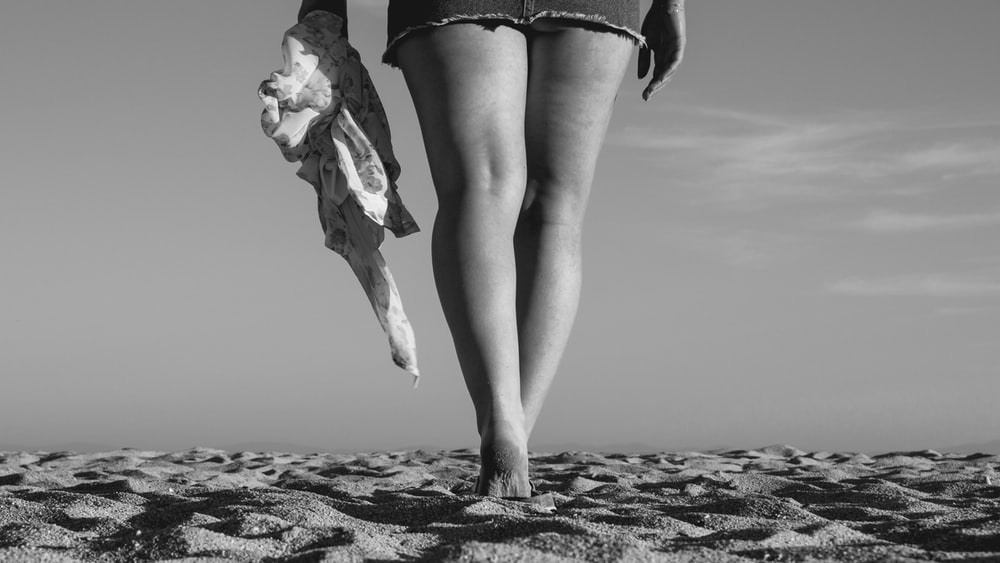 grayscale photography of person walking on sand