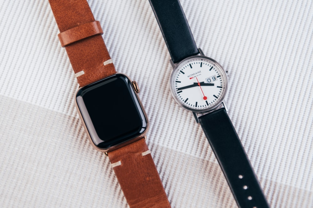 gold Apple Watch and white faced silver framed analog watch