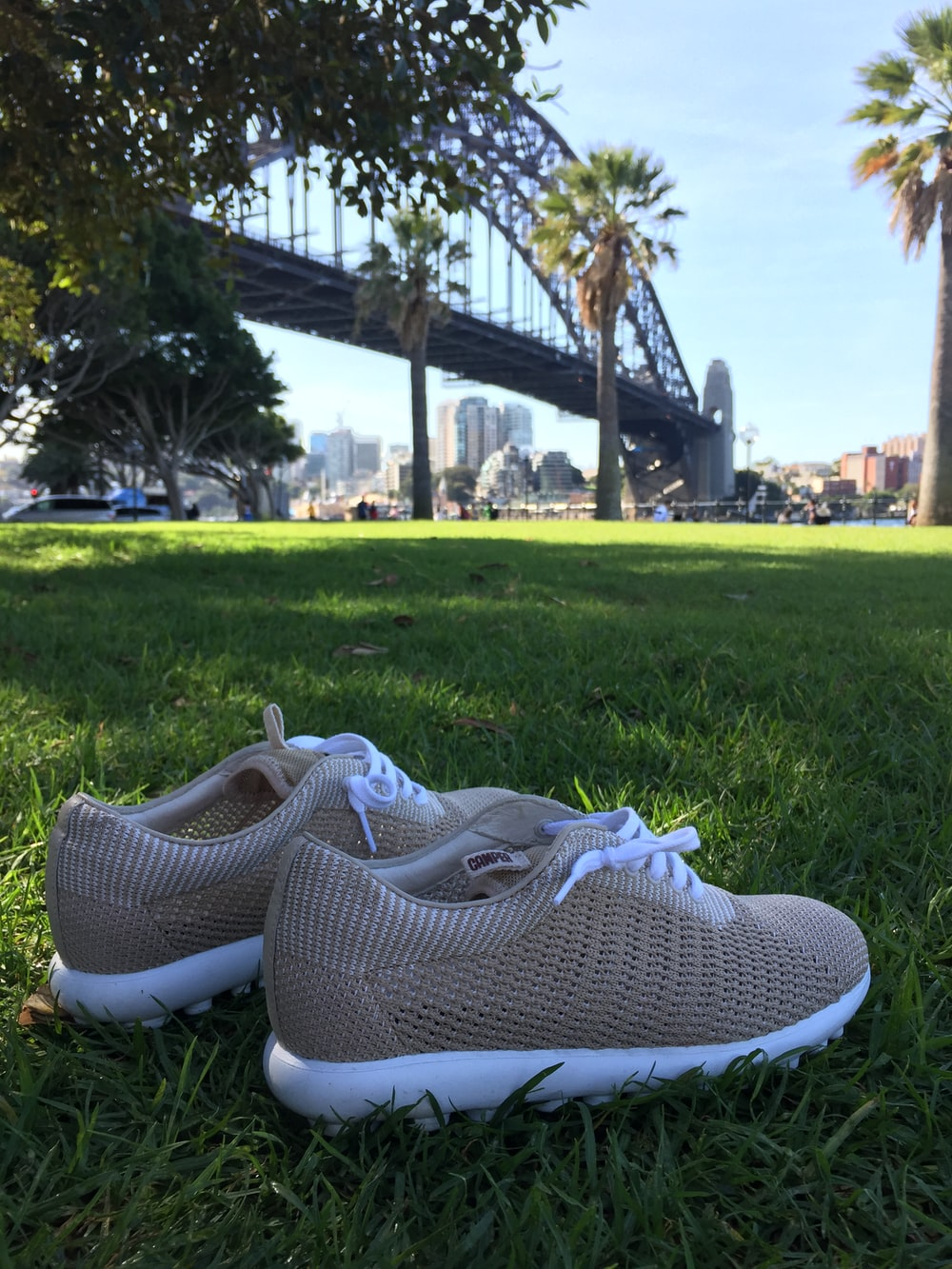 brown low-top shoes on grass near bridge