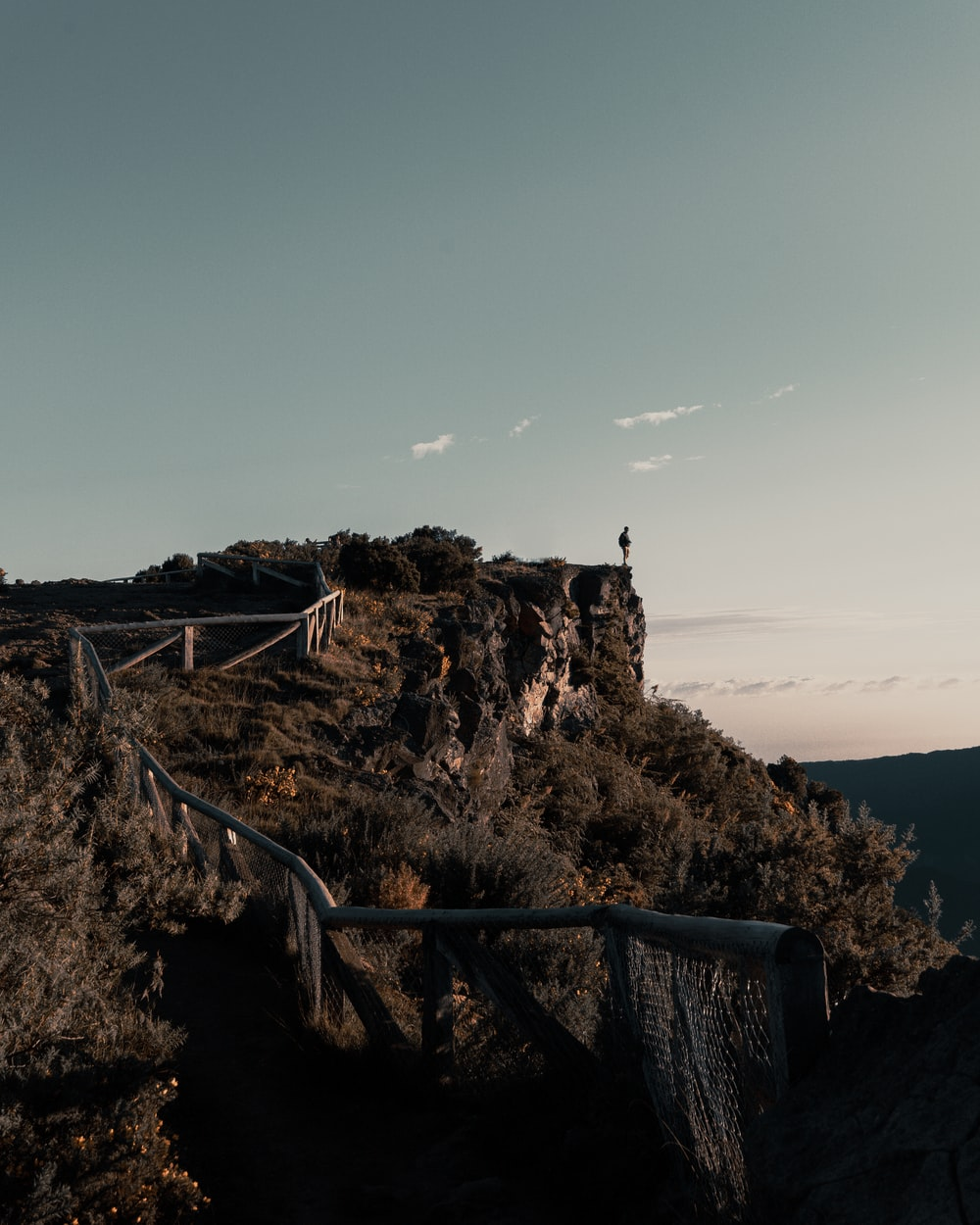 person standing on cliff viewing mountain