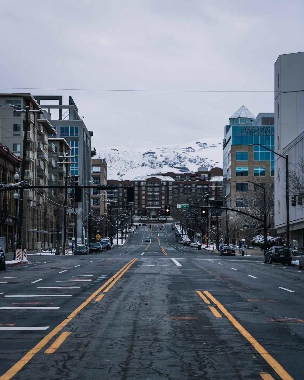 road between buildings under gray sky
