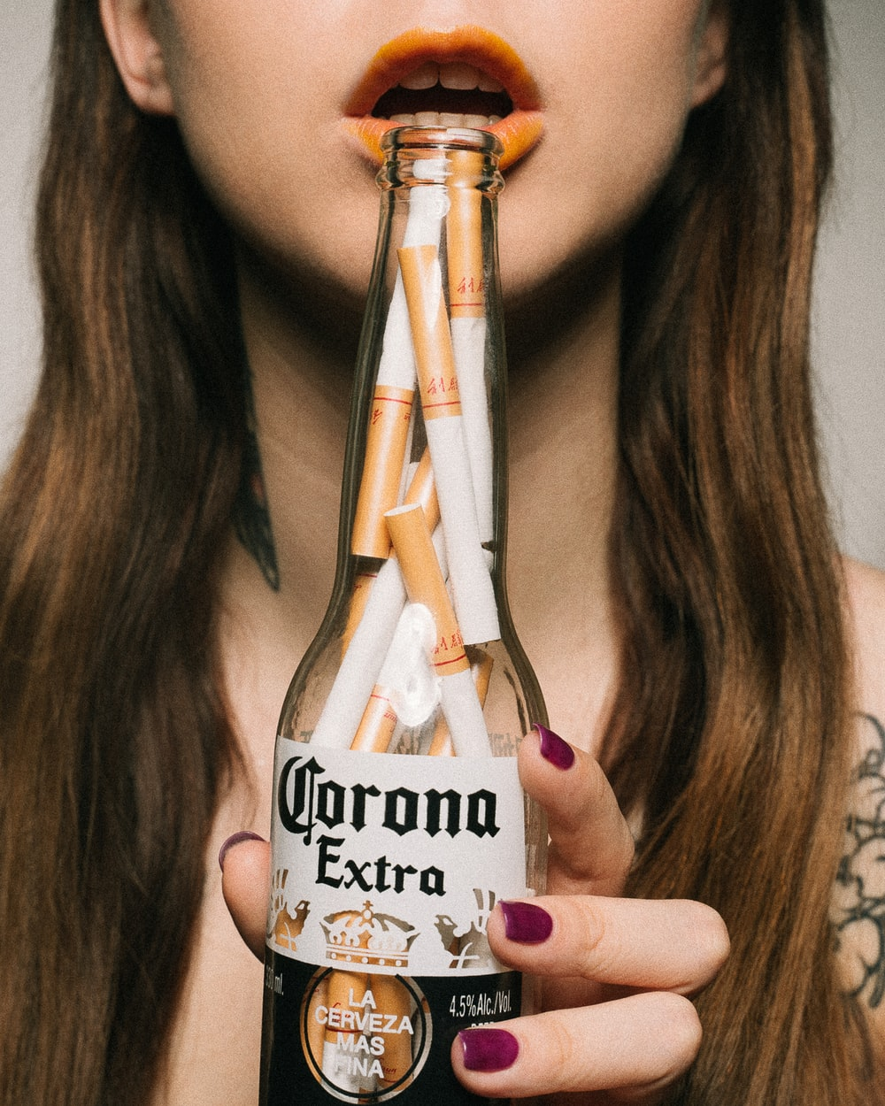 woman holding Corona Extra beer bottle
