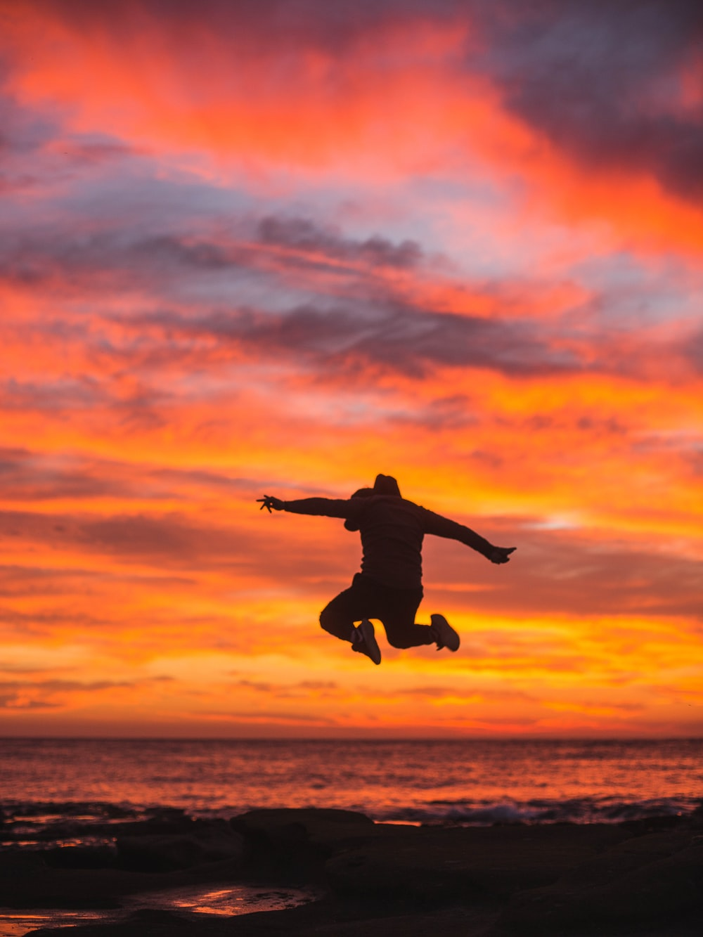 silhouette of person jumping above ground