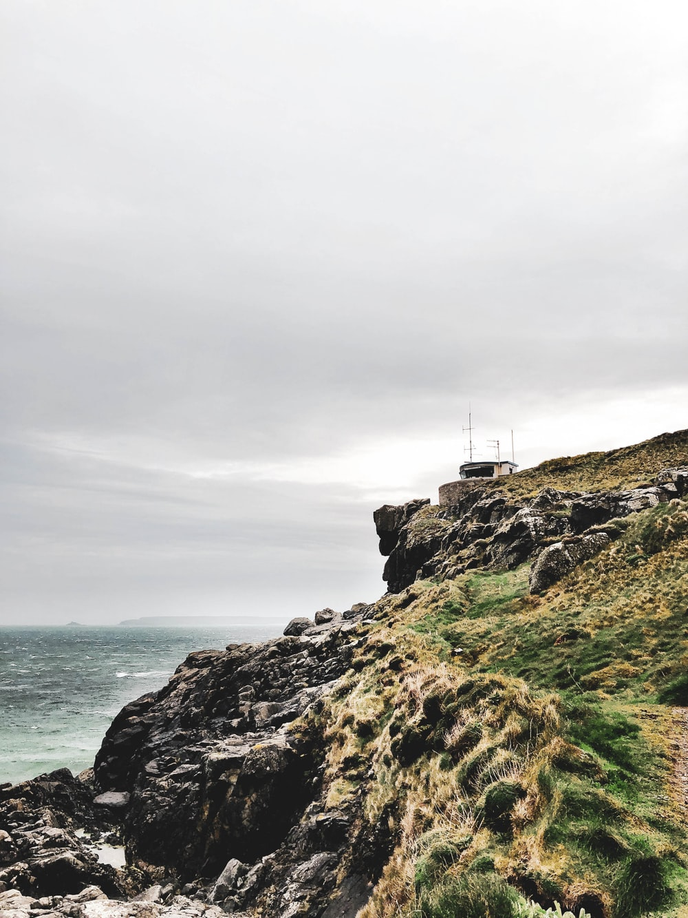house near the edge of island's mountain during day
