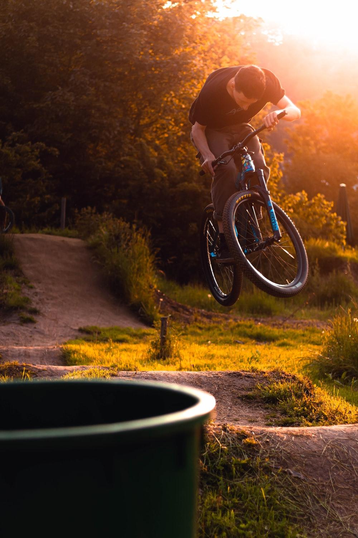 man wearing black crew-neck shirt riding BMX bike mid air