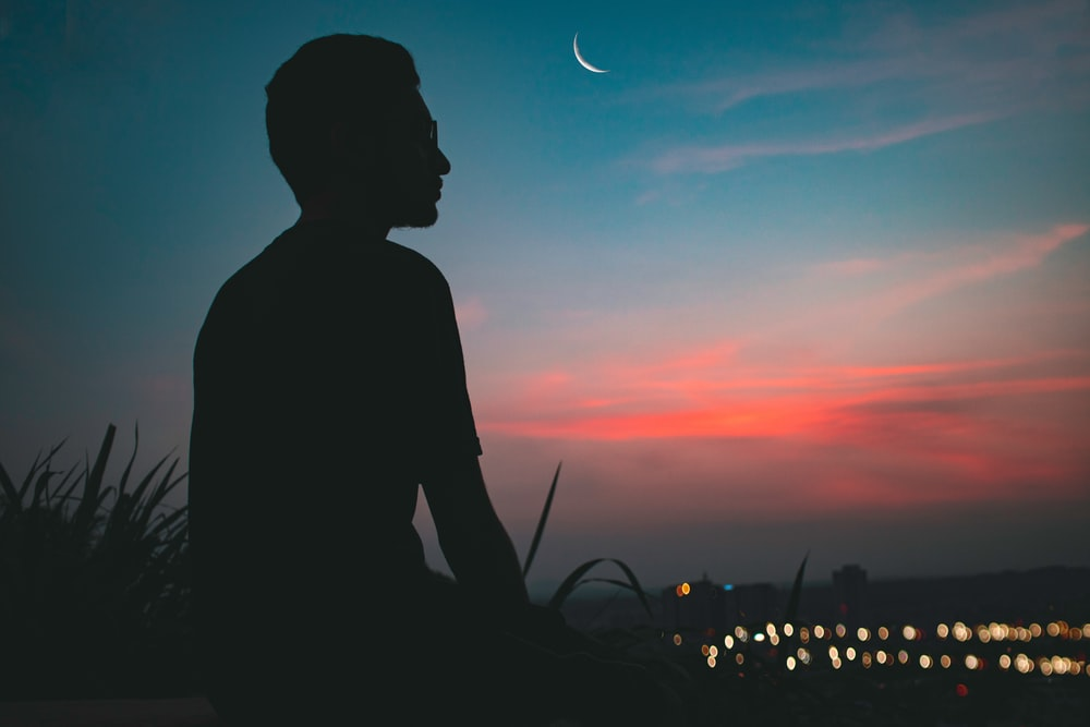 silhouette of man on top of hill overlooking lighted city at dawn