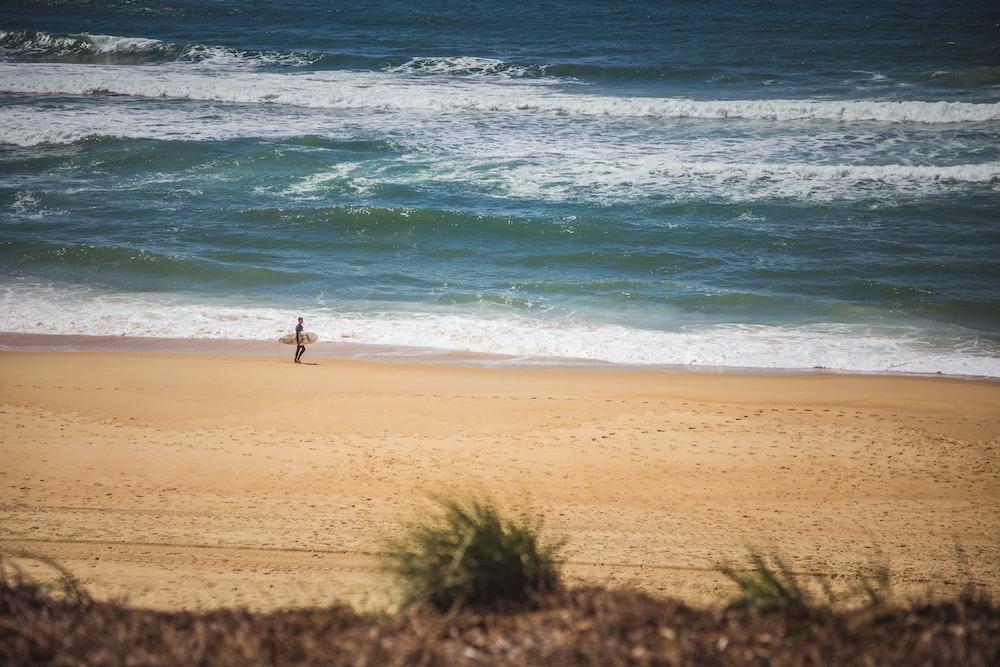 man with surfboard walking in beach