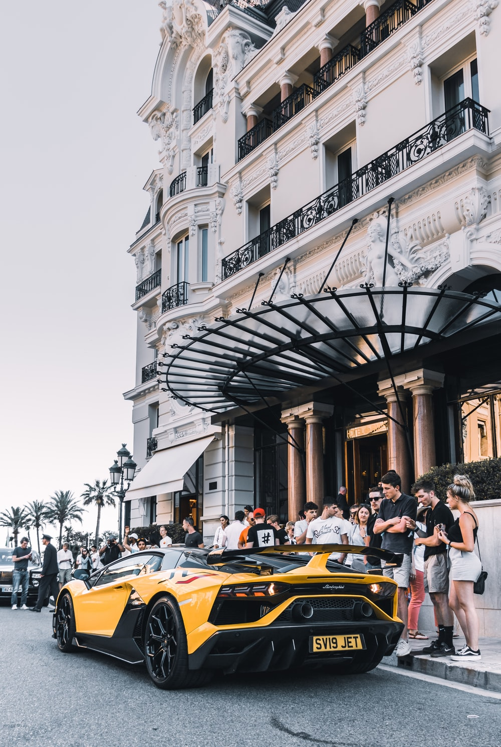 yellow sport car parked on street surrounded group of people