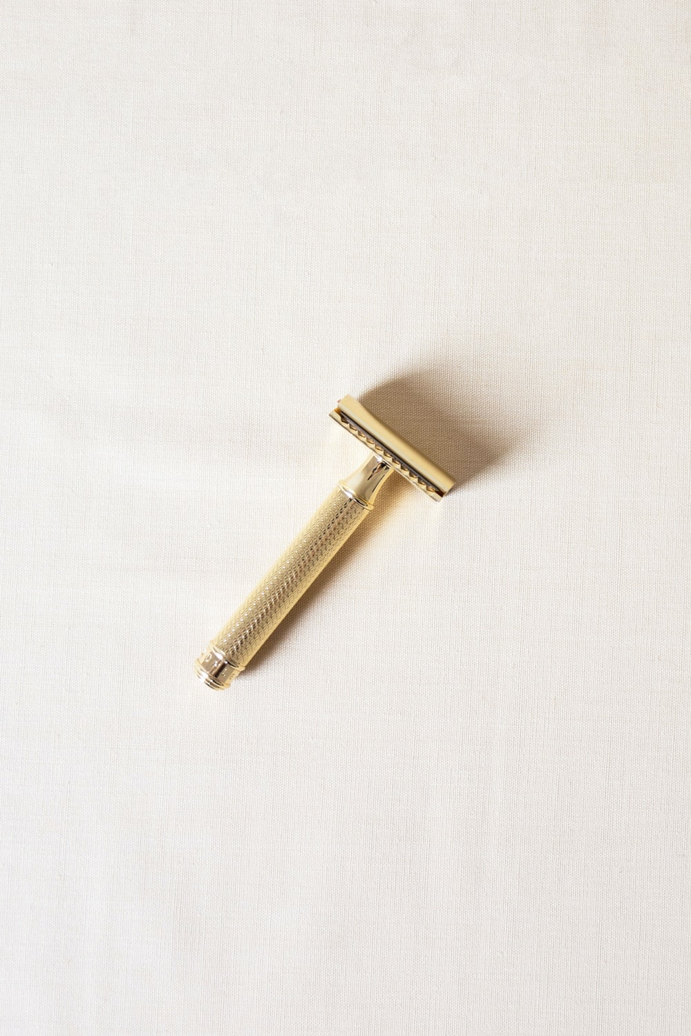 gold-color shaver on white surface