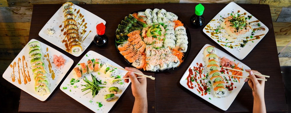 assorted sushi on plates on table