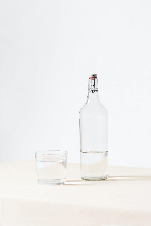 rocks glass beside half empty bottle on white surface