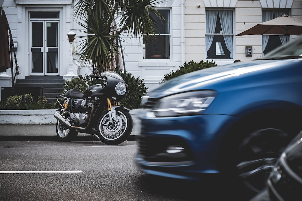 parked black motorcycle in front of white building